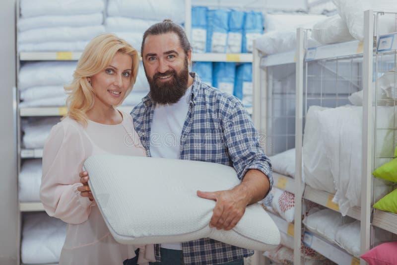 Reizende reife Paare, die neue Kissen kaufen lizenzfreies stockfoto