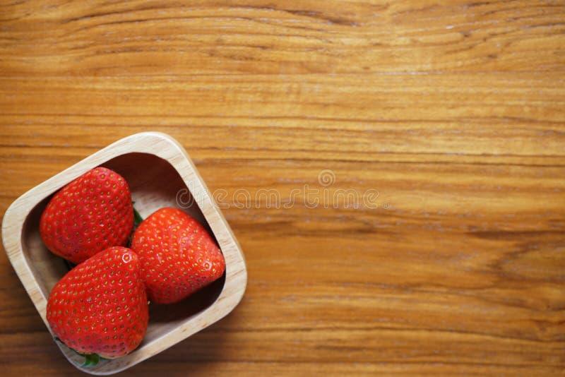 Reizende rote frische reife Erdbeere in der hölzernen Schüssel auf Holztisch, Kopienraum stockfotografie