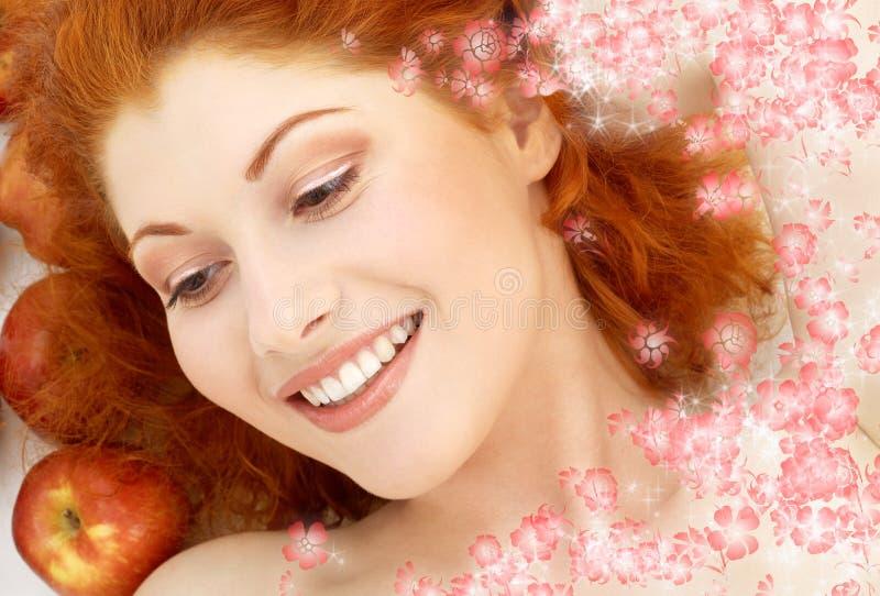 Reizende Rothaarige mit roten Äpfeln und Blumen lizenzfreies stockfoto