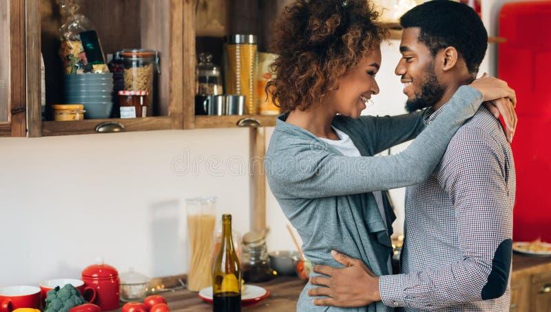 Reizende schwarze Paare, die in der gemütlichen Küche umfassen stockbild