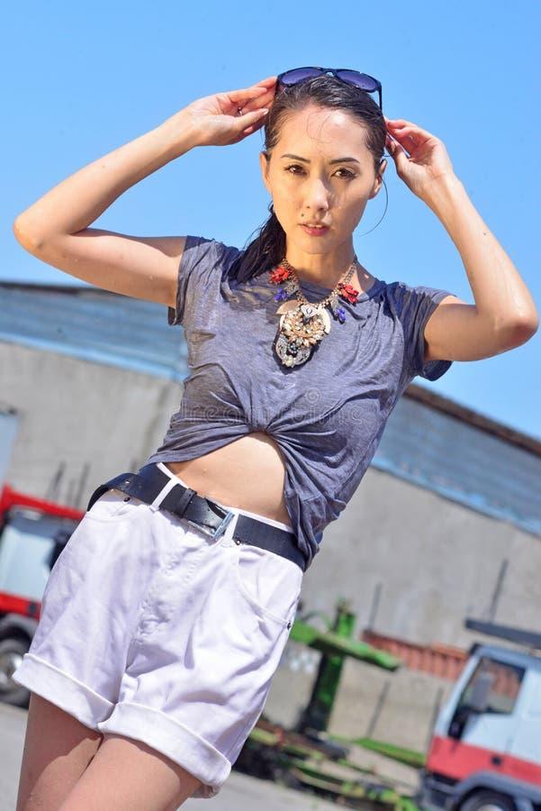 Reizende sexy nasse Frau, ands oben, kurze kurze Hosen, schwarzes langes Haar und öffnen schönes Auge in den Hintergrund-LKWs lizenzfreies stockbild