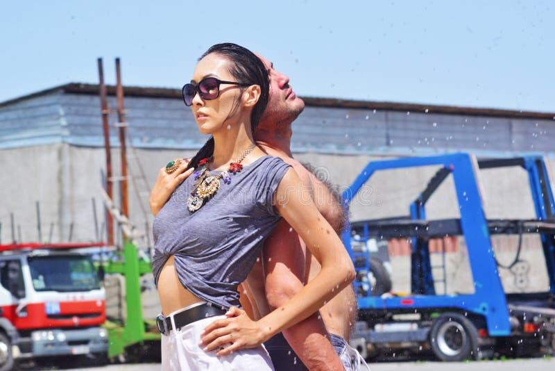 Reizende sexy nasse Frau und Mann, schwarzes langes Haar und Gläser mit Wassertropfen der Hintergrund-LKWs stockbild