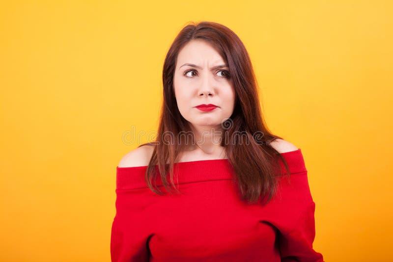 Reizende verwirrte Frau, die weg über gelbem Hintergrund schaut stockfotografie