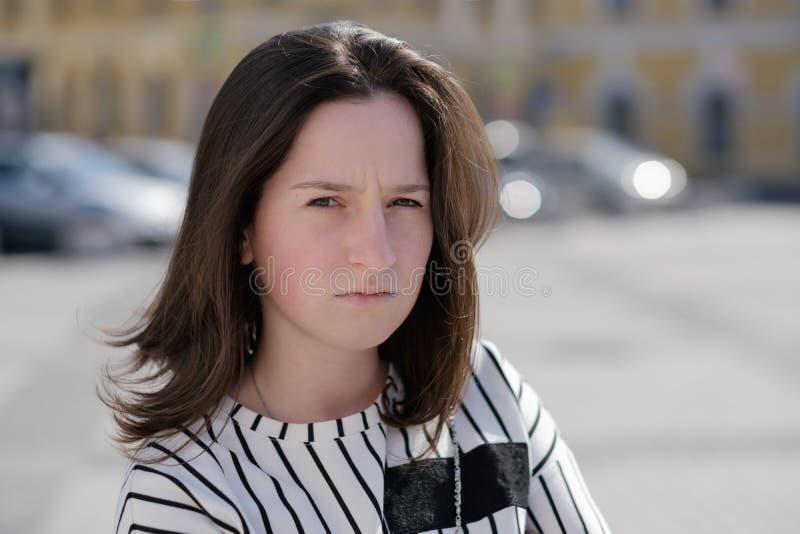 Reizende verwirrte kaukasische Frau, die Kamera mit verwirrtem Ausdruck auf Gesicht betrachtet lizenzfreies stockbild