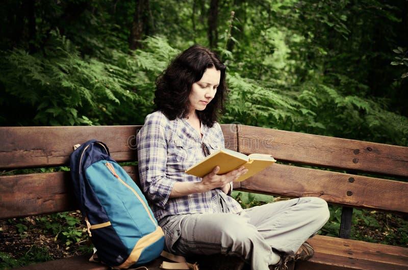 Reizende vrouw die een boek lezen en bij het park ontspannen stock fotografie
