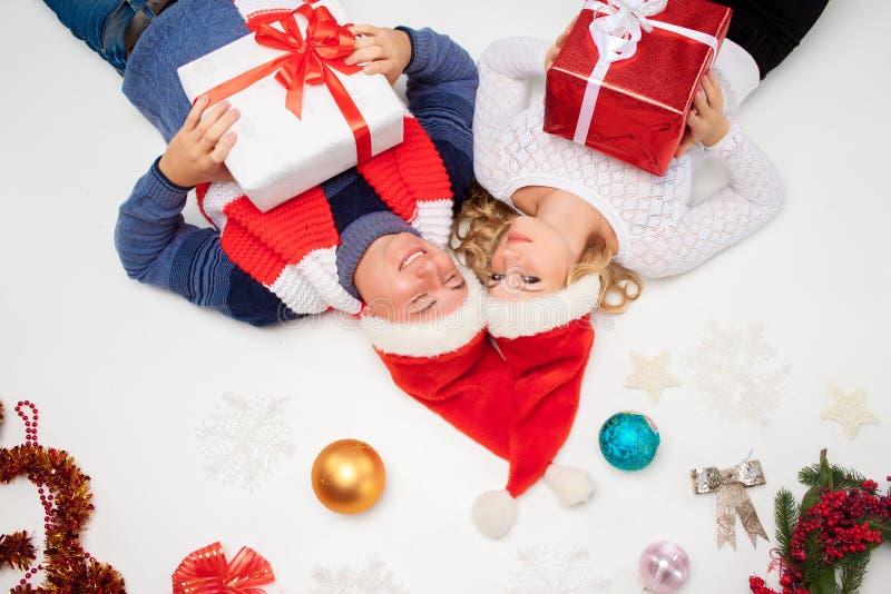 Reizende Weihnachtspaare, die mit Geschenken liegen stockbilder