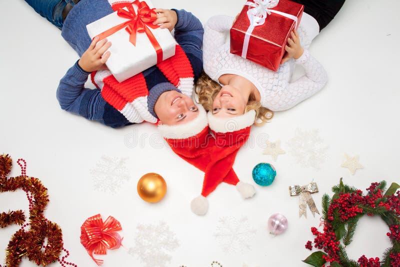 Reizende Weihnachtspaare, die mit Geschenken liegen lizenzfreie stockfotos