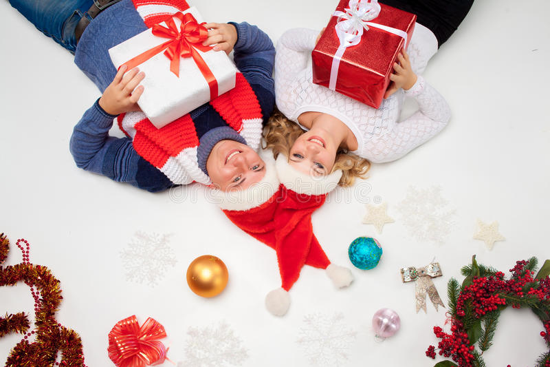 Reizende Weihnachtspaare, die mit Geschenken liegen stockfotos