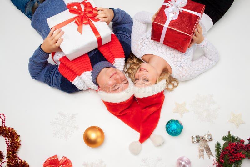 Reizende Weihnachtspaare, die mit Geschenken liegen stockfoto