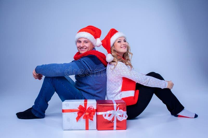 Reizende Weihnachtspaare, die mit Geschenken sitzen stockfotografie