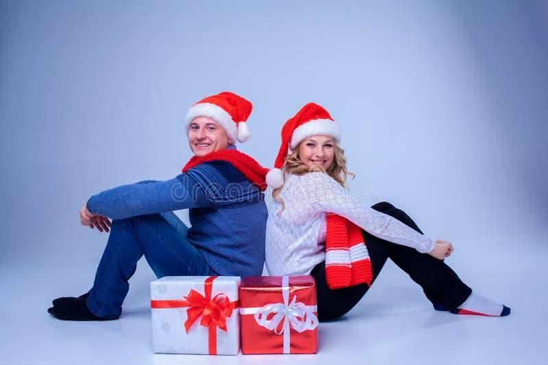 Reizende Weihnachtspaare, die mit Geschenken sitzen lizenzfreies stockbild