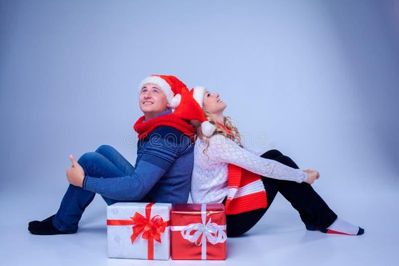 Reizende Weihnachtspaare, die mit Geschenken sitzen lizenzfreie stockbilder