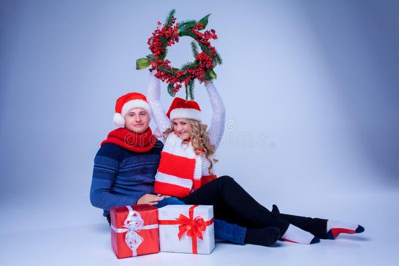 Reizende Weihnachtspaare, die mit Geschenken sitzen stockfoto