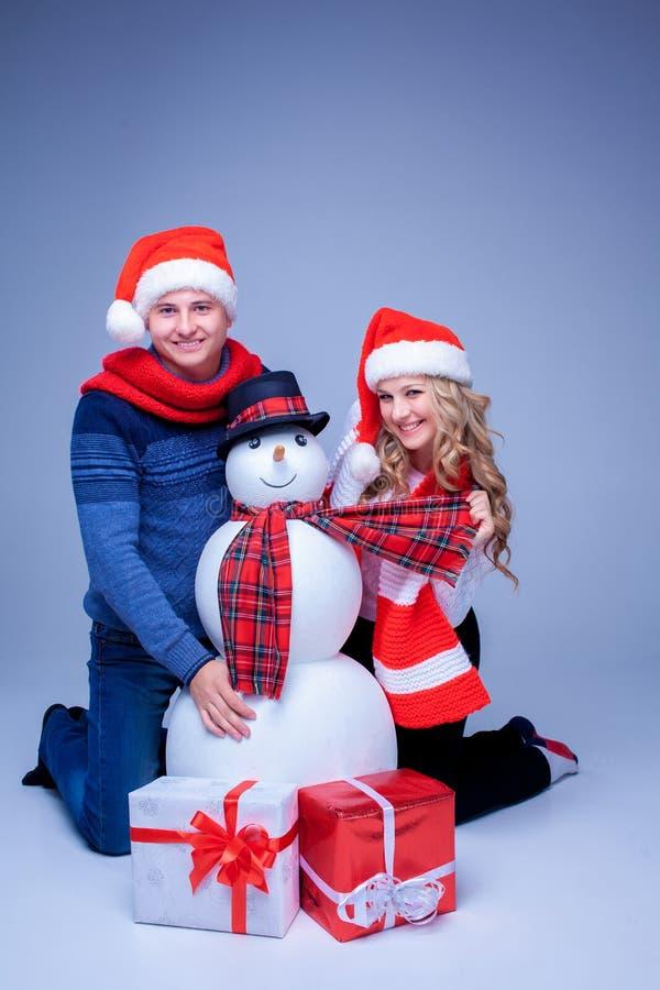 Reizende Weihnachtspaare, die mit Geschenken sitzen stockfotos
