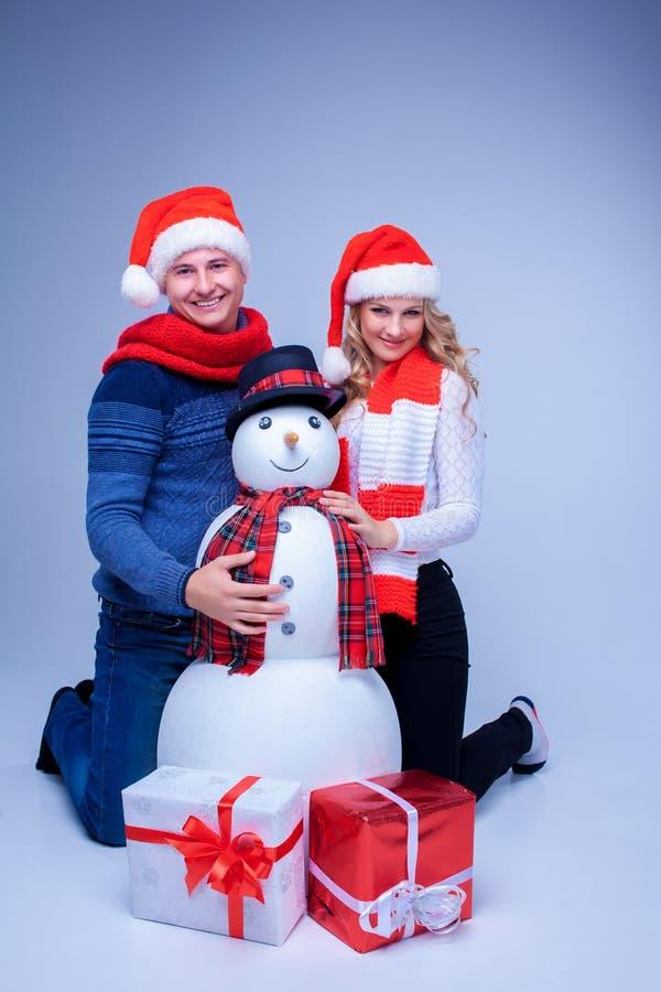 Reizende Weihnachtspaare, die mit Geschenken sitzen lizenzfreies stockfoto