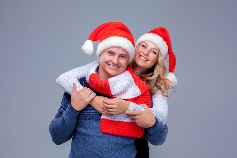 Reizende Weihnachtspaare in Santa Claus-Hüten lizenzfreie stockbilder
