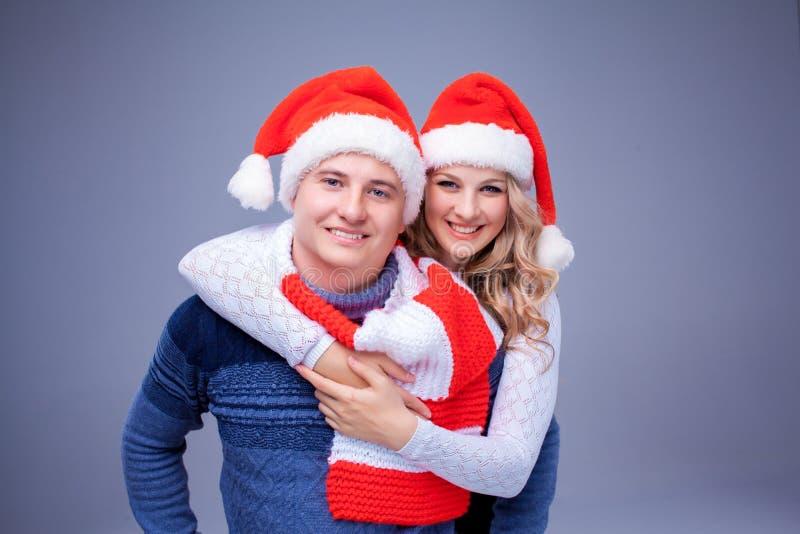 Reizende Weihnachtspaare in Santa Claus-Hüten stockfoto