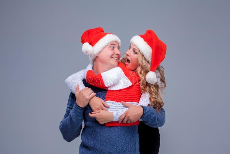 Reizende Weihnachtspaare in Santa Claus-Hüten stockbilder