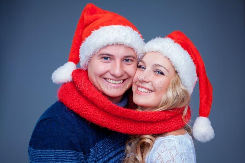 Reizende Weihnachtspaare in Santa Claus-Hüten lizenzfreie stockfotografie
