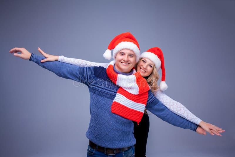 Reizende Weihnachtspaare in Santa Claus-Hüten stockbild