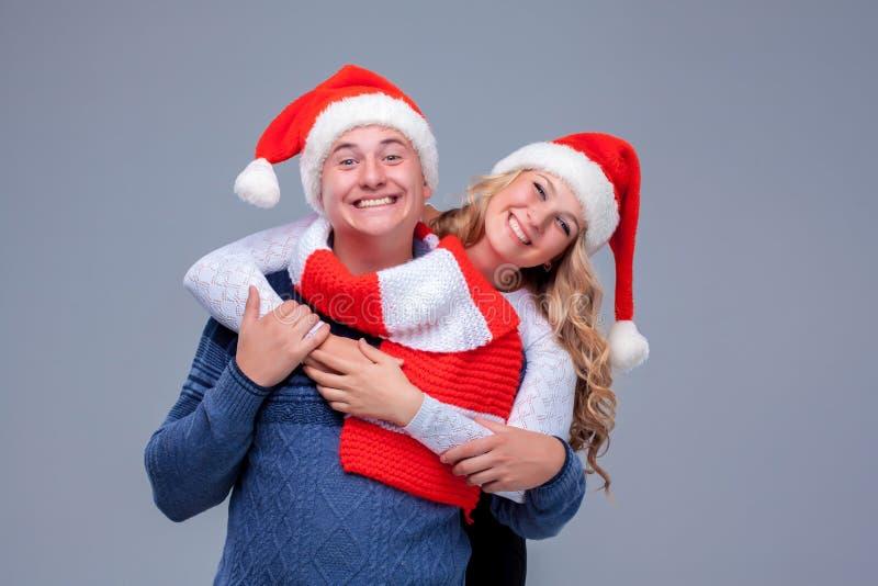 Reizende Weihnachtspaare in Santa Claus-Hüten stockfotografie