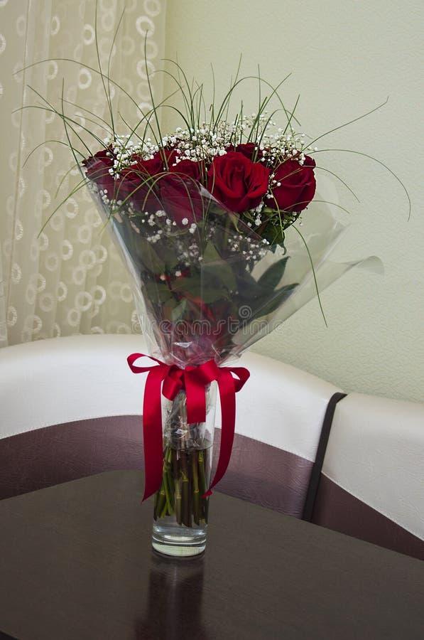 Reizender großer Blumenstrauß mit Blumen von Rosen der weinartigen roten Farbe stehen im Glasvase auf dem Tisch Gr?nbl?tter und - stockbild