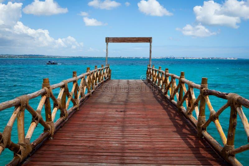 Reizender hölzerner Pier, der zu den Türkis Indischen Ozean führt stockbilder