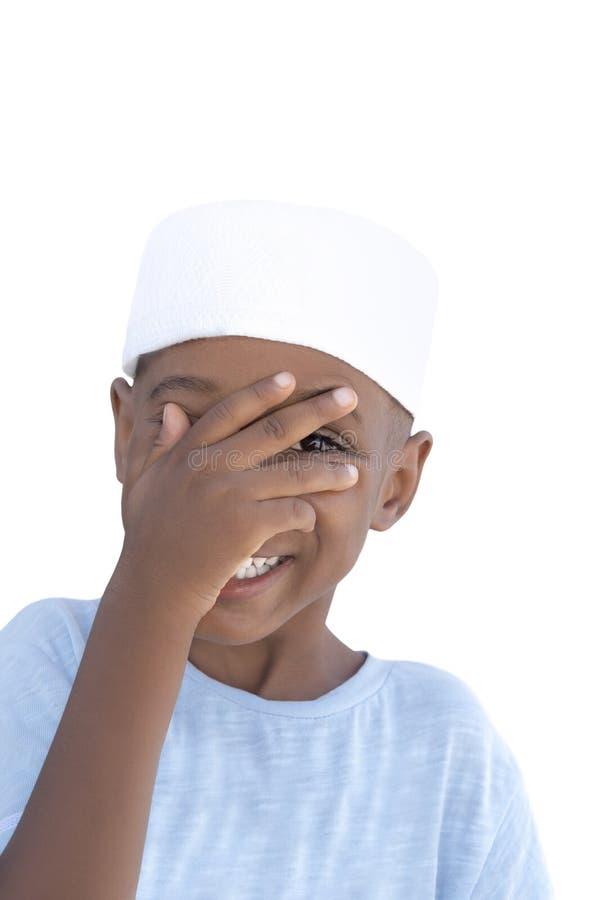Reizender Junge, der Verstecken mit seiner Hand, fünf Jahre alt spielt lizenzfreies stockbild