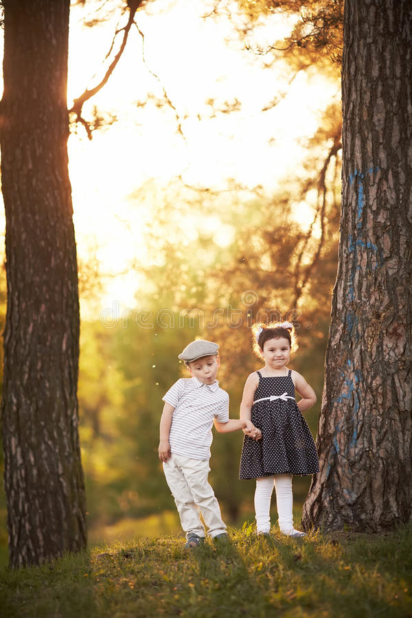 Reizender Junge und Mädchen auf Sonnenuntergang lizenzfreie stockfotos