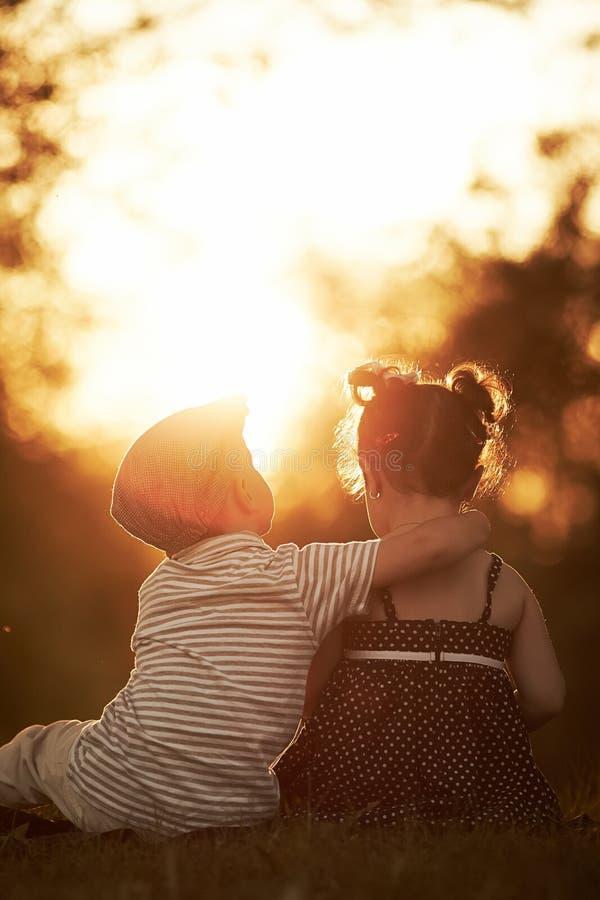 Reizender Junge und Mädchen auf Sonnenuntergang stockfoto