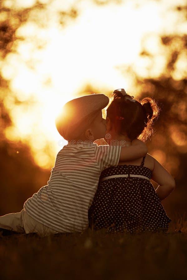 Reizender Junge und Mädchen auf Sonnenuntergang stockfotos