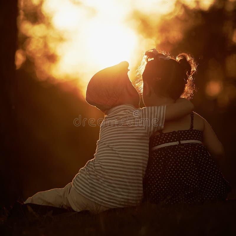 Reizender Junge und Mädchen auf Sonnenuntergang lizenzfreies stockbild