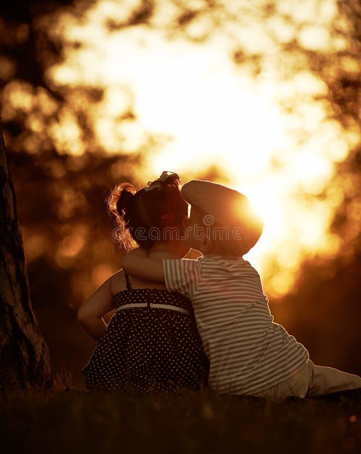 Reizender Junge und Mädchen auf Sonnenuntergang lizenzfreie stockbilder