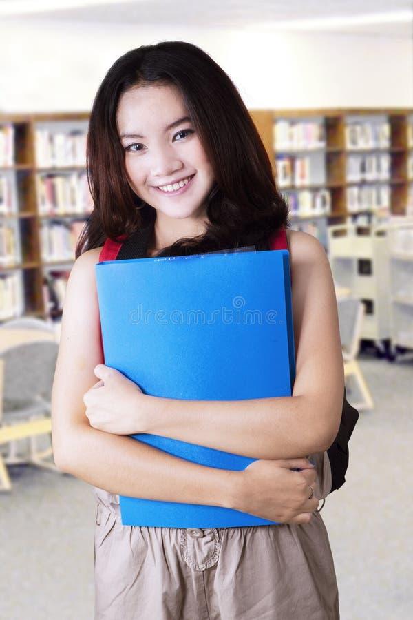 Reizender junger hoher Schüler in der Bibliothek stockfotos