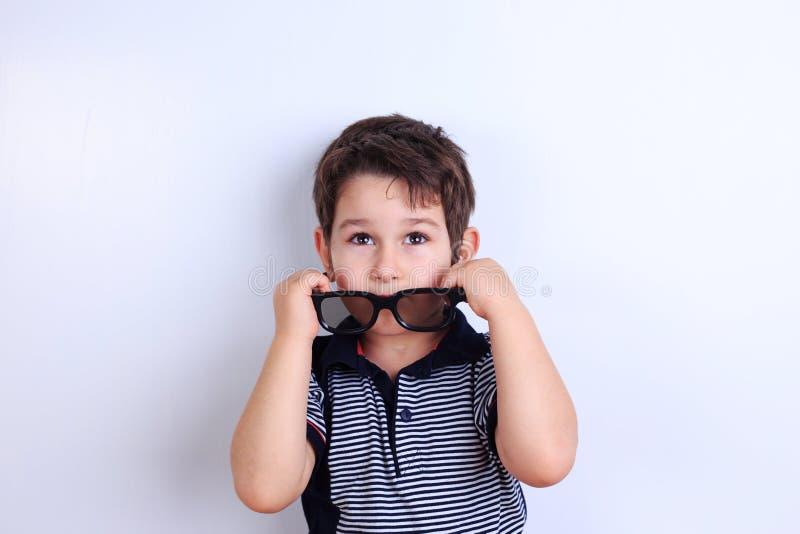 Reizender kleiner Junge, der weg von der Sonnenbrille, Studiotrieb auf Weiß sich setzt lizenzfreie stockfotos