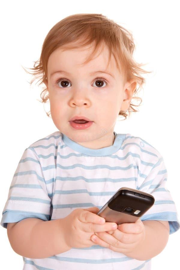 Reizender kleiner Junge mit Telefon stockfotografie