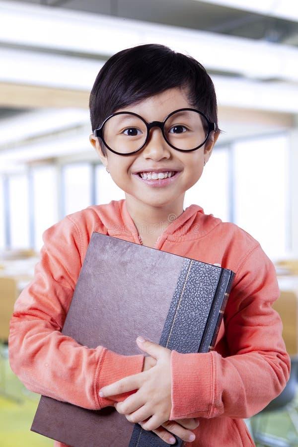 Reizender kleiner Student, der Lehrbuch in der Klasse hält lizenzfreie stockbilder