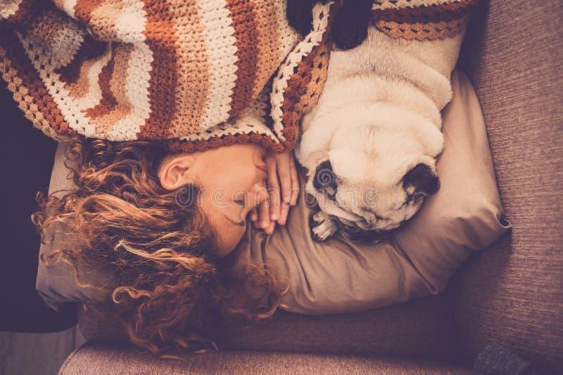 Reizender Paarfrau Pug-Hundeschlaf zusammen zu Hause in einem Angebot und in einer süßen romantischen Szene näher bleiben mit Lie lizenzfreie stockfotos