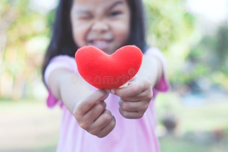 Reizendes asiatisches kleines Kindermädchen, das rotes Herz zeigt und hält lizenzfreie stockfotografie