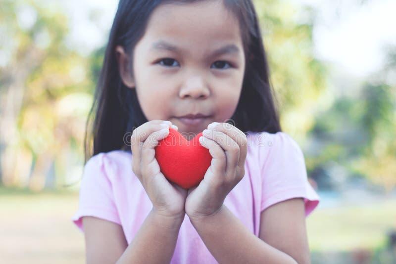 Reizendes asiatisches kleines Kindermädchen mit rotem Herzen lizenzfreies stockbild
