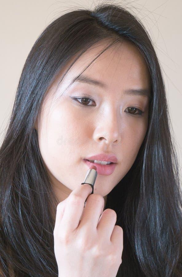 Reizendes asiatisches Modell wendet Lippenstift an lizenzfreies stockbild