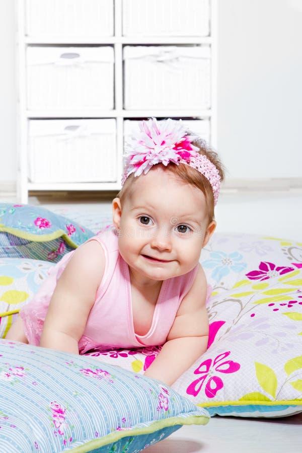 Reizendes Baby, das auf den Kissen liegt stockfotografie