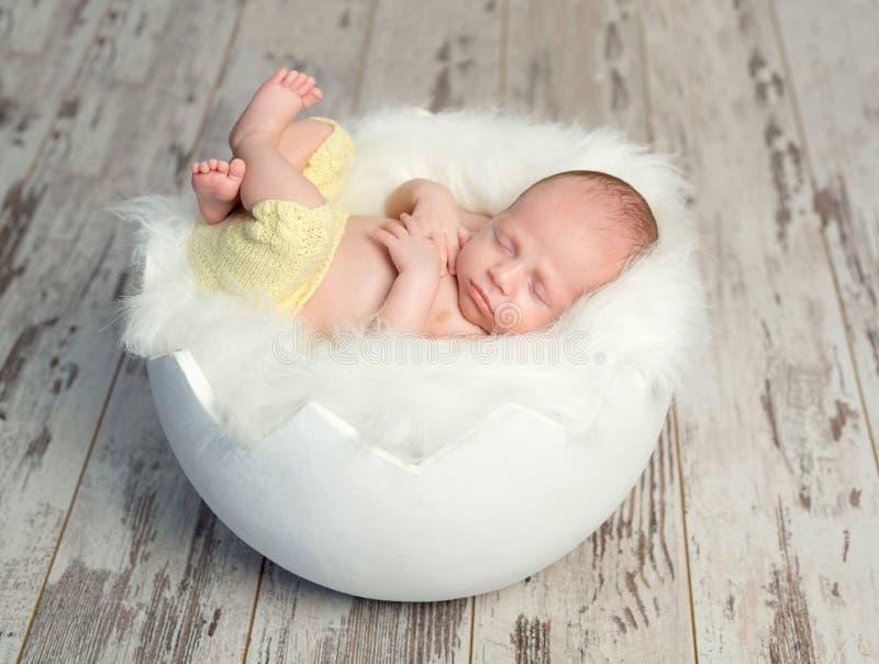 Reizendes Baby in den gelben Hosen auf weißem Feldbett mögen Oberteil stockfoto