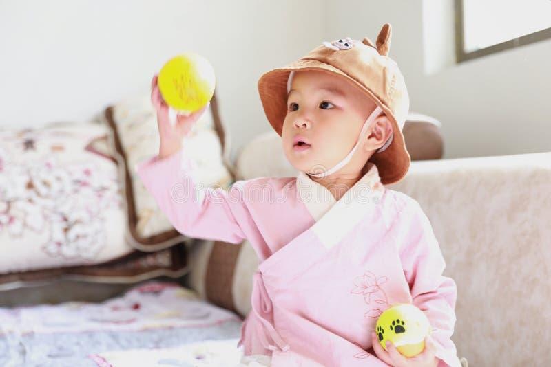 Reizendes Baby mit einem Hutspiel auf Sofa stockbild