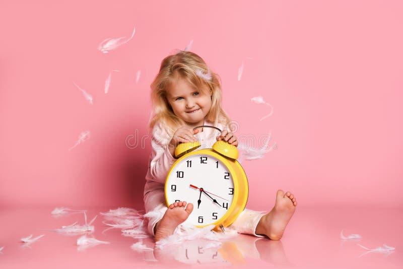 Reizendes blondes Kleinkind, das mit Wecker spielt lizenzfreies stockbild