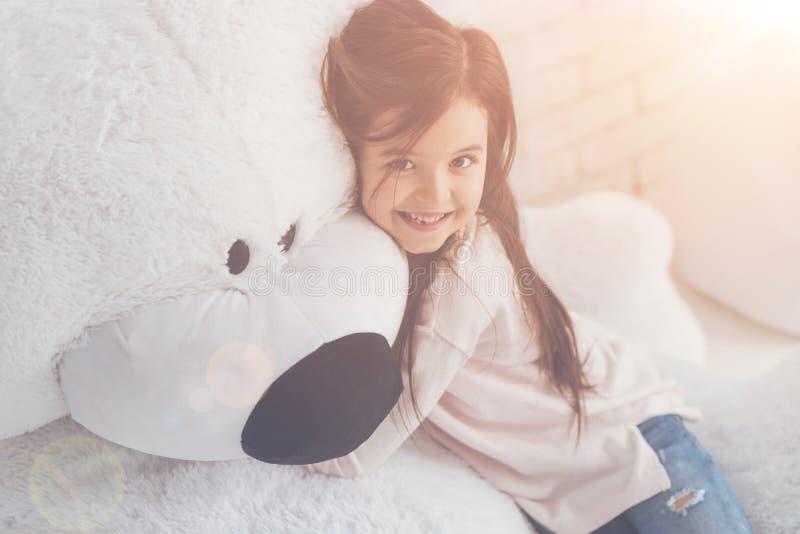 Reizendes emotionales Mädchen, das ihren flaumigen Bären umarmt lizenzfreies stockfoto