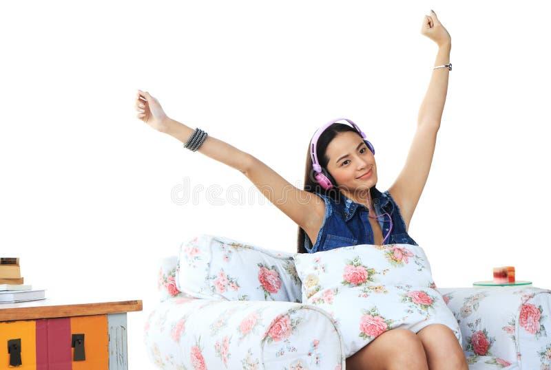 Reizendes hörendes Mädchen eine Musik in den Kopfhörern auf Weiß stockbilder