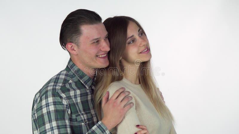 Reizendes junges Paarumarmen, den Kopienraum auf der Seite betrachtend stockbilder