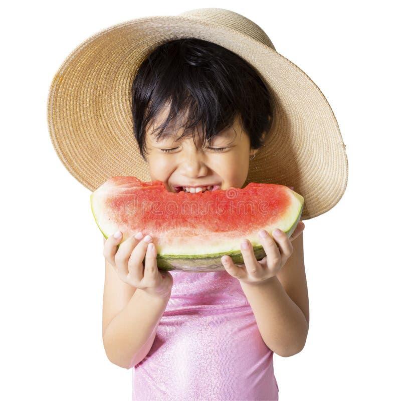 Reizendes Kind, das Wassermelone im Studio isst stockfotografie