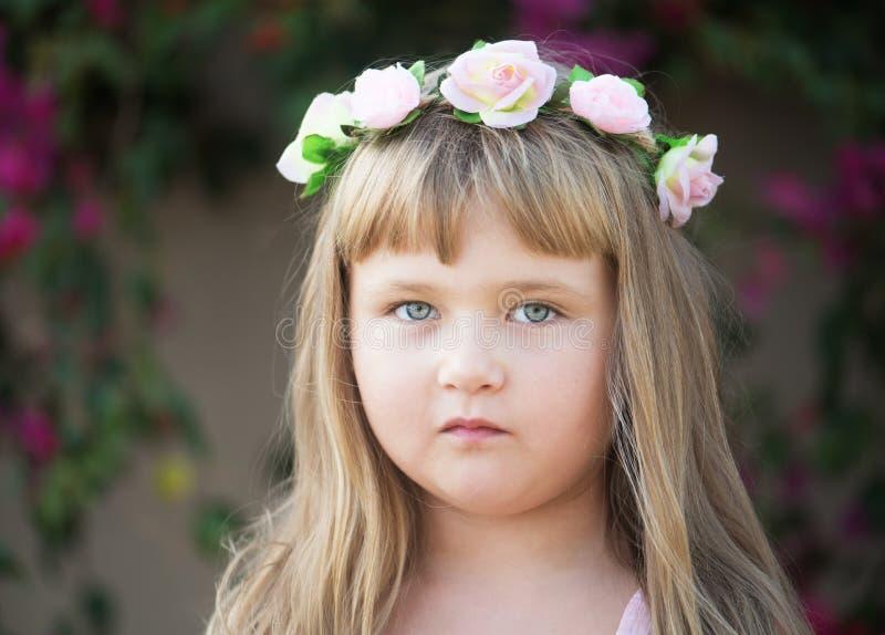 Reizendes kleines Baby mit Gänseblümchenkranz auf ihrem Kopf lizenzfreie stockfotografie